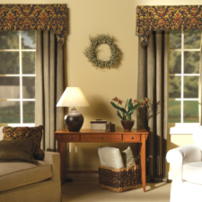 A living room with two windows, each having a patterned soft cornice over stationary panels in a solid, taupe color.