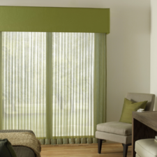 Green sheers under a green fabric wrapped cornice box in a bedroom with earth tones.