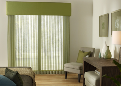 Sheer green curtains let plenty of light come into this room.