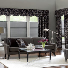 A modern living room with top down bottom up cell shades in the windows and black, patterned draperies on each side of the windows with a fabric valance made out of the same fabric.