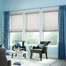 A living room decorated in taupe and blue accessories with taupe wood blinds under taupe and blue draperies.