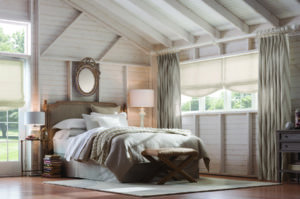 A bedroom with country modern decor and off white roman shades on the windows under two drapery panels in coordinating fabric.