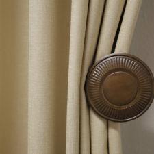 A closeup of a wood tieback holding beige linen draperies.