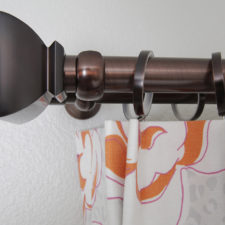 Deep brown drapery hardware and rings holding a white, pink, and orange patterened drapery.