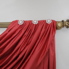 Crystal, flower shaped jewels on a red swag draperies hanging on wood decorative hardware.