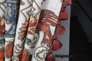 A close up of a patterned drapery with coordinating tassel trim on the edge of it.