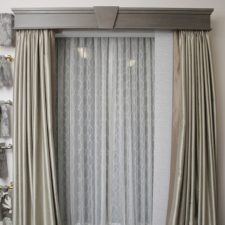 An archway covered with sliding panel vertical blinds under taupe draperies, all under a real wood cornice box.
