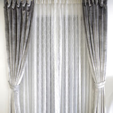 Grey velvet draperies with decorative tiebacks over patterned white sheers all hanging on a decorative rod.