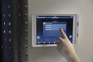 Hand pressing iPad to control the motorized window treatments.