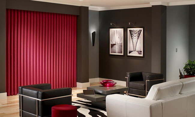 A home theatre in shades of black, white, and gray, with red accents and red custom draperies covering a large screen.