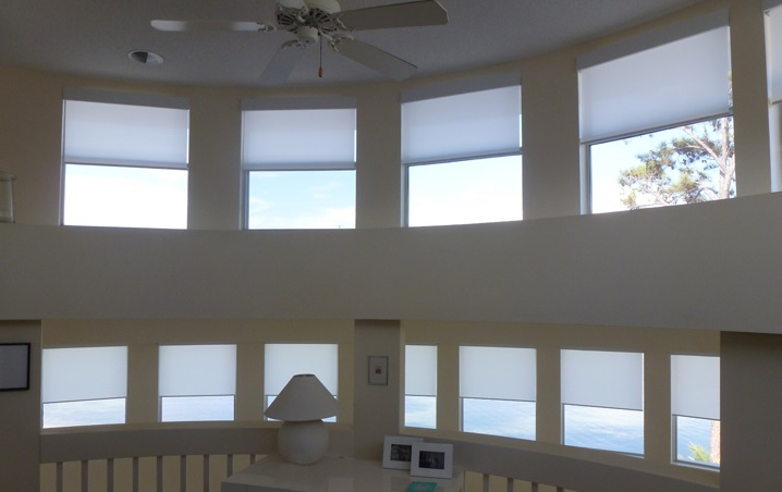 Roller shades on ten windows on a high wall facing a lake.