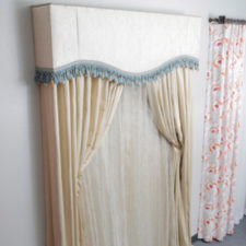 Different types of draperies over sheers. One is a swag, one is sheers with draperies and a fabric wrapped cornice, and the third is grommet top draperies and sheers.