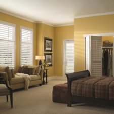 White faux wood shutters with slats partially open and the ability to swing on hinges in a bedroom.