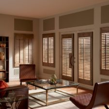 Wood plantation shutters over three windows and two doors with open slats in a living room.