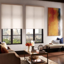 Two semi-opaque motorized roller shades half open in a living room overlooking downtown