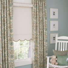 Half open beige roller shade layered with decorative drapery panels in a nursey.