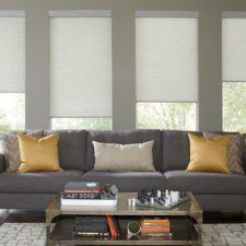 Four roller shades raised at different heights behind a dark grey couch in a living room.