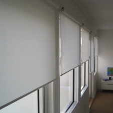 Side shot of motorized roller shades half open in a bedroom.