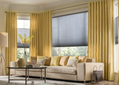 This sunny yellow room is tied together perfectly with yellow drapery panels and roller shades over the large windows.