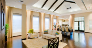 A bright, open living room with high ceilings, large windows, and an airy combination of yellow window treatments
