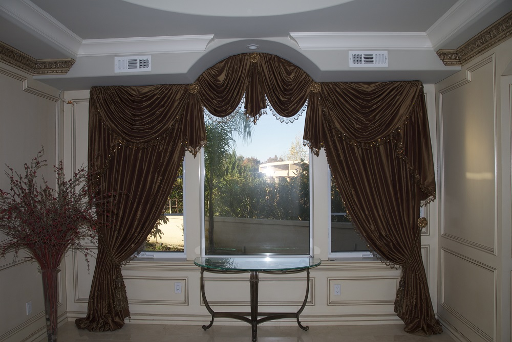Beautifully hung window swag with elegant tassels over a three piece window