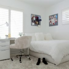 Window shutters partially open to bring light into a child's white bedroom.