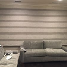 Grey roman shade in a modern designed living room in the down position.