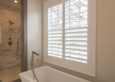 Split shutters in the guest bathroom allow tilt on the bottom half only for privacy and light.