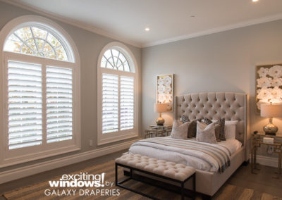 The guest bedroom's shutters look beautiful and clean while still allowing plenty of natural light and complementing the arched tops.