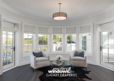 Matching roller shades over the windows and doors give this nook in the master bedroom a finished and beautiful look.