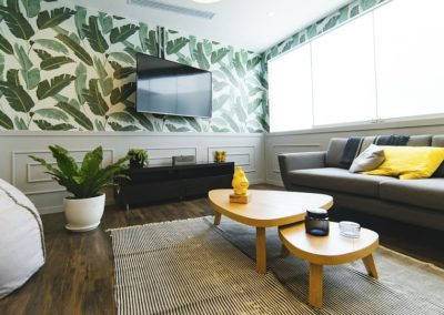 Leaves on the wallpaper and leaves on the indoor plant make this room feel much more exciting.