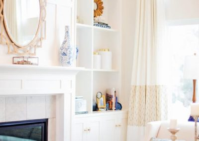 The mirror above the fireplace reflects much of the window light back into the small room.
