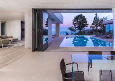 Sliding panels and draperies open up to a beautiful private pool