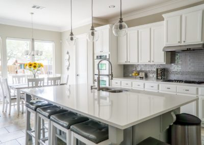 This kitchen would be bland without textured backsplash and nailhead bar stools.