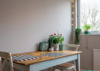Dining nook with distressed wood bench, wood textures and plants
