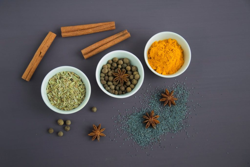 Star anise, cinnamon sticks and assorted spices in white bowls