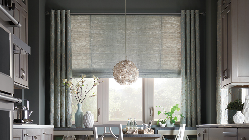 Sage green layered natural shades and draperies cover a window in a dining room