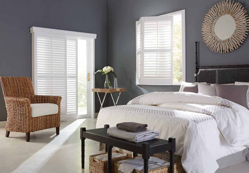 Modern white shutters over a sliding door and window in a bedroom