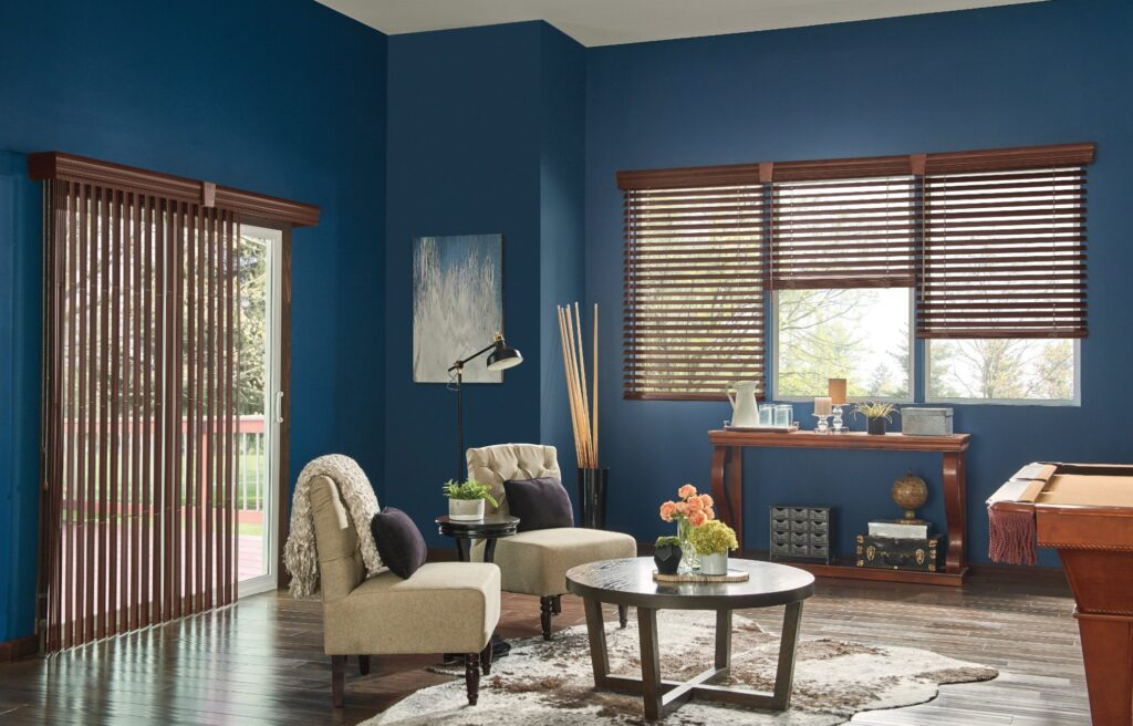 Modern vertical wooden blinds cover a sliding door, while horizontal matching blinds cover three windows in a living room.