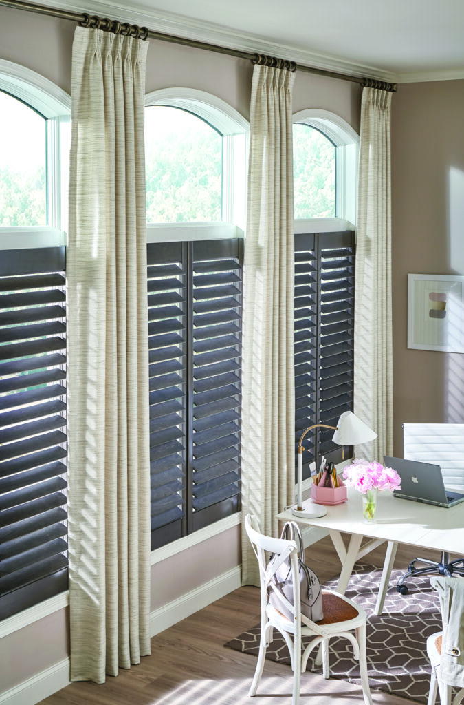 Shutters cover the lower half of windows with a bare top, surrounded by drapery panels