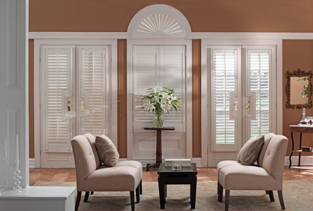 white shutters cover two french doors and an arch over a central window