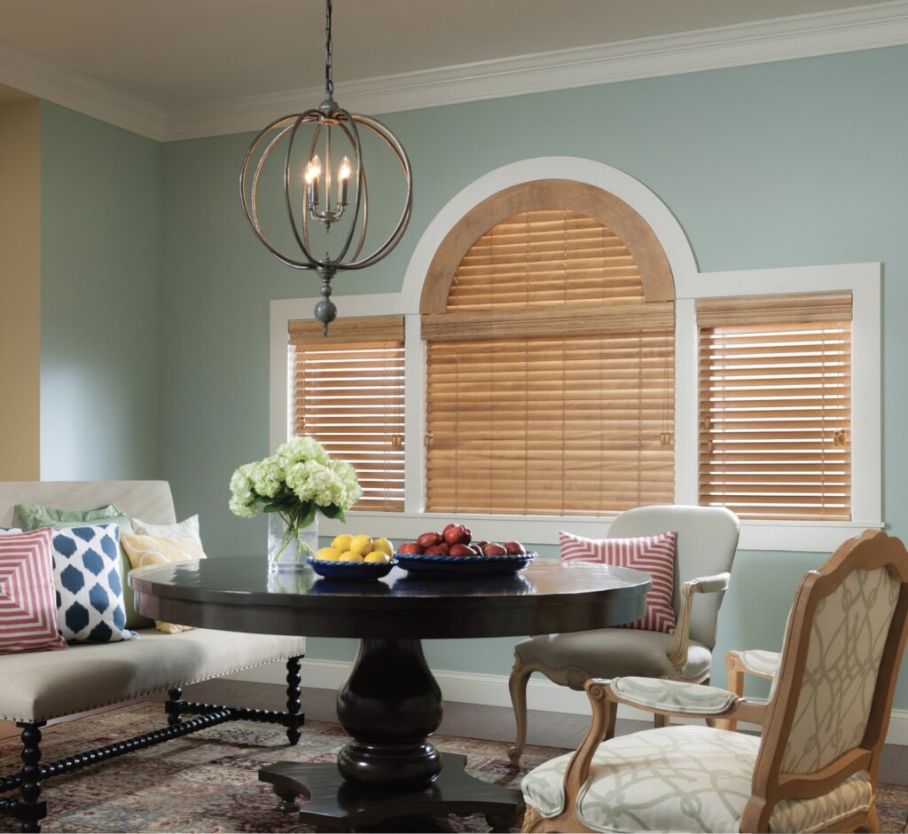 Wooden blinds cover two side and one main window with an arched top