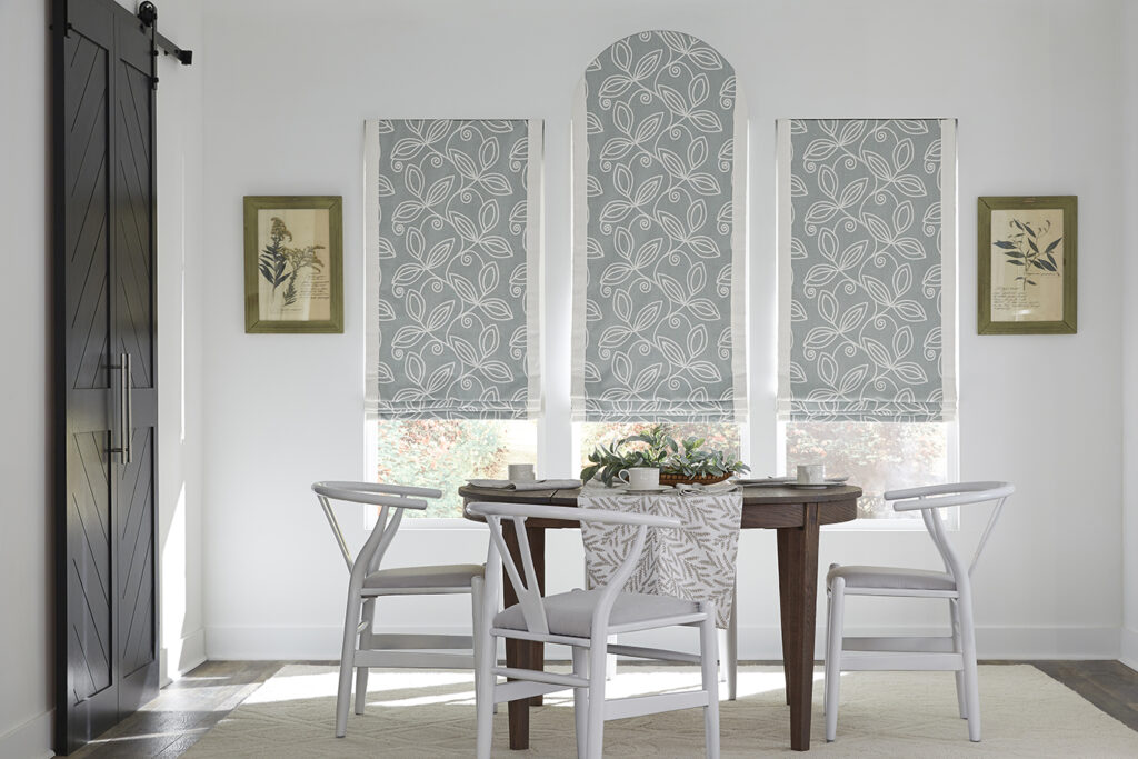 Light blue patterned roman shades cover three dining room windows, the center with an arched window